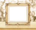 Blank victorian style golden frame with sparkling gold bokeh wall and wooden table, business concept presentation.