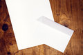 Blank white envelope and paper on wooden desk Royalty Free Stock Photo