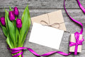 Blank white greeting card and envelope with purple tulips and gift box Royalty Free Stock Photo