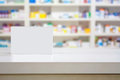 Blank white medicine package on counter with blur shelves of drug in the pharmacy drugstore Stock Image