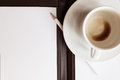 Blank white notebook pen and cup of coffee on table Royalty Free Stock Images