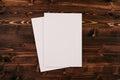Blank white paper A4, envelope on vintage brown wooden board. Mock up for branding identity.