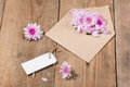 Blank white paper tag with brown envelope and pink flowers on wo