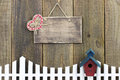 Blank wood sign with plaid heart hanging over white picket fence with birdhouse rustic red red and blue Stock Photos