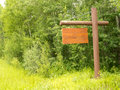Blank wooden sign board dense green forest edge empty rustic with copyspace ready for your text message hanging on pole with Royalty Free Stock Photography