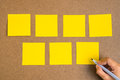 Blank yellow sticky notes on brown wood with hand Royalty Free Stock Photo