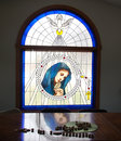 Blessed virgin mary stained glass with reflection and rosary of on table beautiful Stock Image