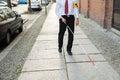 Blind man walking on sidewalk holding stick wearing armband Stock Images