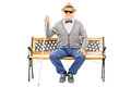Blind senior man seated on bench isolated on white background Royalty Free Stock Photo