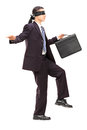 Blindfolded young businessman with briefcase walking full length portrait of isolated on white background Stock Photos
