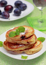 Blinis (from white flour, with plum) on plate Stock Photos