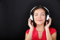 Blissful beautiful woman listening to music young asian with her eyes closed on a set of headphones and smiling with pleasure Stock Images