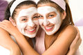 Blissful girls applying mask hugging each other Royalty Free Stock Photo