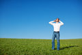 Blissful man enjoying his music outdoors standing in a fresh green field under a sunny blue sky Stock Photography