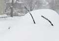 Blizzard background car covered in snow with windshield wiper blades sticking out Stock Photography