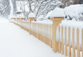 Blizzard heavy snow accumulation on unfinished picket fence Royalty Free Stock Photos