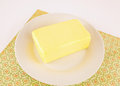 Block of butter on white plate atop printed floral mat Royalty Free Stock Photo