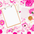 Blogger of freelancer composition. Workspace with clipboard, notebook, pen and pink roses on white background. Flat lay, top view. Royalty Free Stock Photo