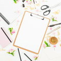 Blogger or freelancer workspace with clipboard, notebook, flowers and accessories on white background. Flat lay, top view.