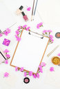 Blogger or freelancer workspace desk with clipboard, notebook, pink flowers and accessories on white background. Beauty blog conce