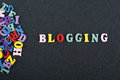 BLOGGING word on black board background composed from colorful abc alphabet block wooden letters, copy space for ad text