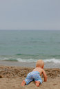 Blond baby crawling to the sea Royalty Free Stock Photo
