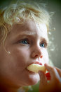 Blond baby girl eating corn flakes Royalty Free Stock Photo