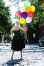 Blond with balloons out in the sun Royalty Free Stock Image