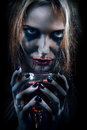 Blond bloody witch with glass on black background toned image Stock Photos