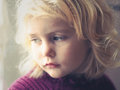 Blond  blue eyed little girl looking out the window Royalty Free Stock Photo