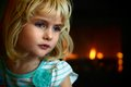 Blond  blue eyed little girl sitting in front of a fireplace Royalty Free Stock Photo