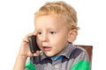 Blond boy careful talking on a cell phone with pointed glance Stock Photos