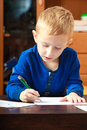 Blond boy child kid with pen writing on piece of paper at home happy childhood doing homework Royalty Free Stock Images