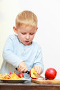 Blond boy child kid preschooler with kitchen knife cutting fruit apple at home happy childhood Royalty Free Stock Image