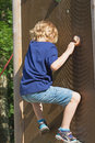 The blond boy climbs the climbing wall in summer day Royalty Free Stock Photos