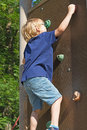 The blond boy climbs the climbing wall in summer day Stock Image