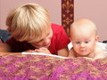 Blond boy with his newborn baby brother indoor Royalty Free Stock Image