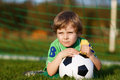 Blond boy of playing soccer with football on football field outdoors Stock Photos