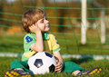 Blond boy of playing soccer with football on football field outdoors Stock Image