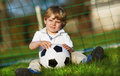 Blond boy of playing soccer with football on football field outdoors Stock Photo