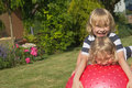 Blond boys are playing with gymnastic ball two attractive red outdoors Royalty Free Stock Photo