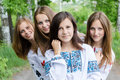 4 blond & brunette girlfriends young beautiful women having fun posing happy smile standing together in forest or park Royalty Free Stock Photo