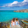 Blond and brunette kid girls sitting on beach port sister in formentera summer vacation Stock Images