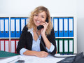 Blond businesswoman at office speaking with client at phone Royalty Free Stock Photo