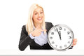 Blond businesswoman sitting and pointing on a wall clock Stock Photography