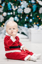 Blond Caucasian baby boy child with blue eyes in red Santa Claus costume sitting by New Year tree Royalty Free Stock Photo