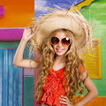 Blond children happy tourist girl beach hat and sunglasses with straw on a tropical house Royalty Free Stock Photography