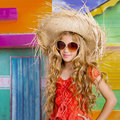 Blond children happy tourist girl beach hat and sunglasses with straw on a tropical house Stock Photography