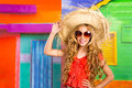 Blond children happy tourist girl beach hat and sunglasses with straw on a tropical house Stock Image