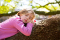 Blond children kid girl having a nap lying on a tree branch Royalty Free Stock Photos